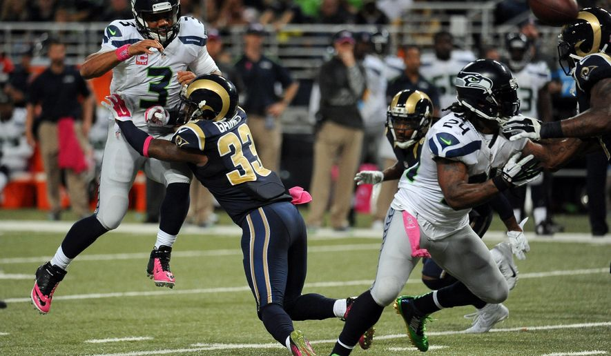 Seattle Seahawks quarterback Russell Wilson, left, is hit by St. Louis Rams cornerback E.J. Gaines (33) while throwing during the fourth quarter of an NFL football game Sunday, Oct. 19, 2014, in St. Louis. The Rams won 28-26. (AP Photo/L.G. Patterson)
