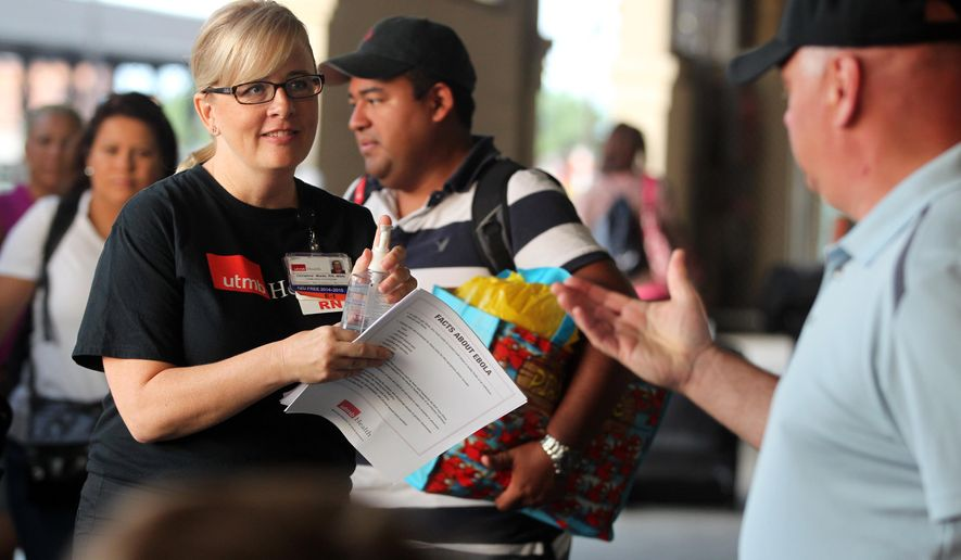 Christine Wade, a registered nurse at the University of Texas Medical Branch, greets Carnival Magic passengers disembarking in Galveston, Texas on Sunday, Oct. 19, 2014. Nurses met passengers with Ebola virus fact sheets and to answer any questions.  A Dallas health care worker was in voluntary isolation in her cabin aboard the cruise ship because of her potential contact with the Ebola virus. (AP Photo/The Galveston County Daily News, Jennifer Reynolds)