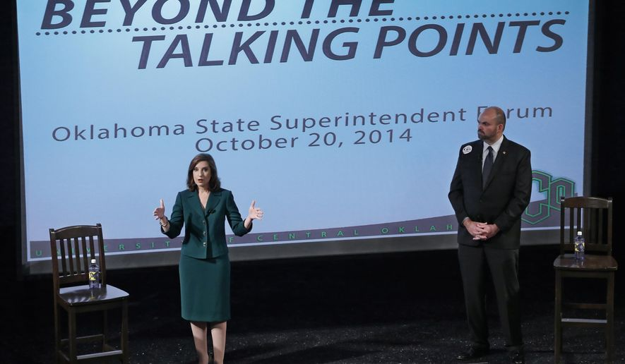 Democratic nominee for the office of Superintendent of Public Instruction, John Cox, right, listens as Republican nominee Joy Hofmeister, left, answers a question during a debate in Edmond, Okla, Monday, Oct. 20, 2014. (AP Photo/Sue Ogrocki)