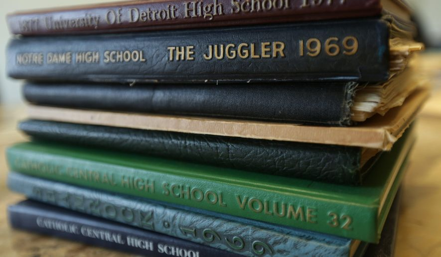 A Jan. 28, 2014 photo shows some high school year books that are part of the archives of the Detroit Catholic School Heritage Project, an archive of submissions about Detroit-area Catholic schools, in in Lathrup Village, Mich. The Detroit Catholic Schools Heritage Project will display yearbooks, letter sweaters, school mascots and photos at a building near Ladywood High School. It also plans to create a replica classroom with items from past and present Detroit-area Catholic schools. (AP Photo/The Detroit Free Press, Romain Blanquart)  DETROIT NEWS OUT;  NO SALES