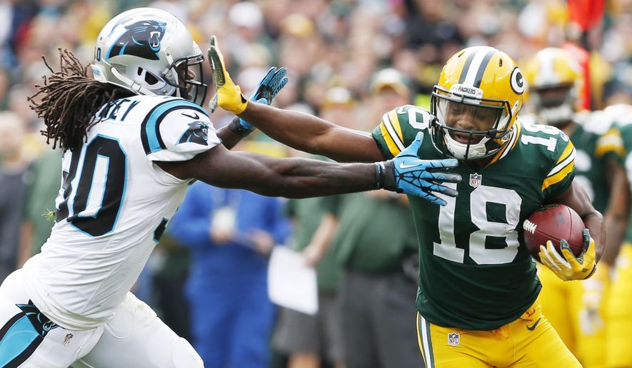 Green Bay Packers' Randall Cobb (18) tries to get past Carolina Panthers' Charles Godfrey after a catch during the first half of an NFL football game Sunday, Oct. 19, 2014, in Green Bay, Wis. (AP Photo/Mike Roemer)