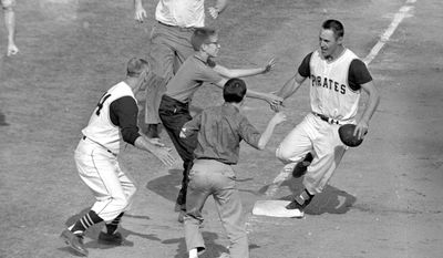 FILE - In this Oct. 13, 1960, file photo, Pittsburgh Pirates fans rush onto the field to congratulate second baseman Bill Mazeroski as he rounds third base after hitting his World Series-winning home run against the New York Yankees in the bottom of the ninth inning at Forbes Field in Pittsburgh, Pa. Mazeroski will have several personal items auctioned at the Louisville Slugger Museum & Factory in November, including the jersey he wore in Game 7 of the 1960 World Series. (AP Photo/File)