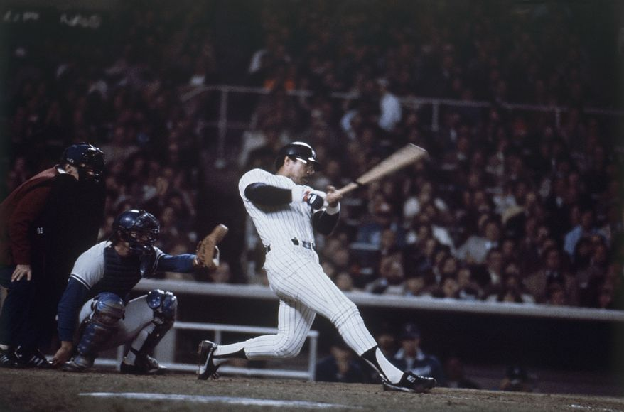 New York Yankees outfielder Reggie Jackson blasts home run number three during the sixth and final game of the World Series at Yankee Stadium in New York on Oct. 18, 1977. (AP Photo)