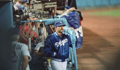 Injured Los Angeles Dodgers star Kirk Gibson watches the action from the dugout at Dodger Stadium, Saturday, Oct. 15, 1988, Los Angeles, Calif. A leg injury kept Gibson out of the first game of World Series against the Oakland A's. (AP Photo/Bob Galbraith)