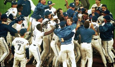 Toronto Blue Jays members mob teammate Joe Carter after his game winning home run in bottom of 9th in game 6 of World Series, October 23, 1993. (AP Photo)
