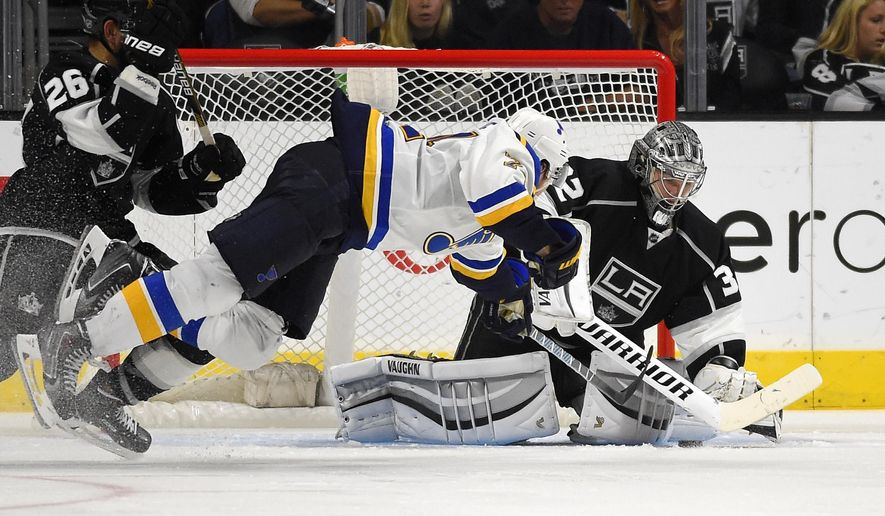 Los Angeles Kings goalie Jonathan Quick, right, stops a shot by St. Louis Blues right wing T.J. Oshie, center, as defenseman Slava Voynov, of Russia, looks on during the third period of an NHL hockey game, Thursday, Oct. 16, 2014, in Los Angeles. (AP Photo/Mark J. Terrill)