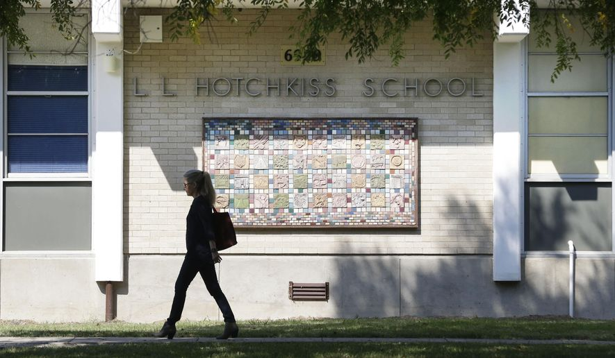 A woman walks by the front of L.L. Hotchkiss School Monday, Oct. 20, 2014, in Dallas. Some students on the the Ebola isolations list have returned to the school after completing a 21-day period of monitoring. (AP Photo/LM Otero)