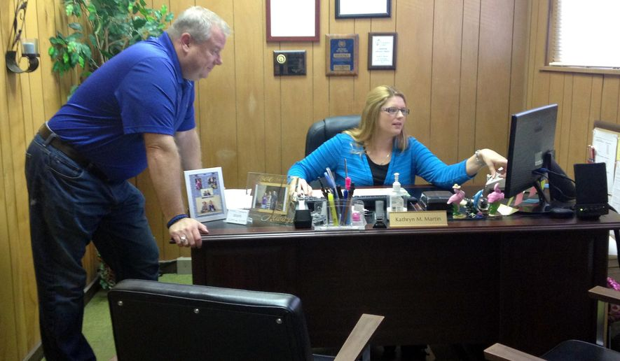 In this Oct. 17, 2014 photo, Knight Township Trustee Kathryn Martin looks over August requests for Vectren assistance with case manager Tony Goben in Martin's Evansville, Ind., office. Some public assistance organizations in southwestern Indiana say many Vectren electricity customers are seeking help paying big bills from the utility correcting ones that were underestimated during the summer. (AP Photo/The Evansville Courier & Press, Jessie Higgins)