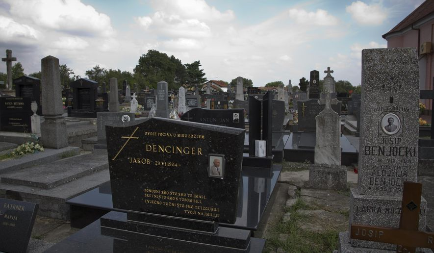 This July 28, 2014, photo shows Jakob Denzinger's portrait on the tombstone of his empty grave in Cepin eastern Croatia. Denzinger is among dozens of death camp guards and suspected Nazi war criminals who collected millions of dollars in Social Security payments despite being forced out of the United States according to an Associated Press investigation. (AP Photo/Darko Bandic)