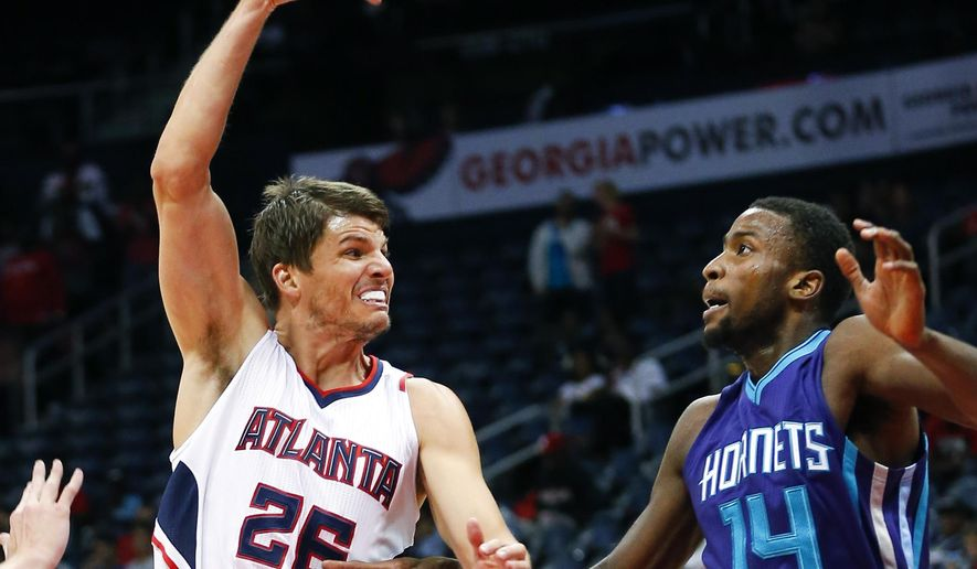 Atlanta Hawks guard Kyle Korver (26) passes the ball as Charlotte Hornets forward Michael Kidd-Gilchrist (14) defends during the first half of an NBA pre-season basketball game Monday, Oct. 20, 2014, in Atlanta.  (AP Photo/John Bazemore)