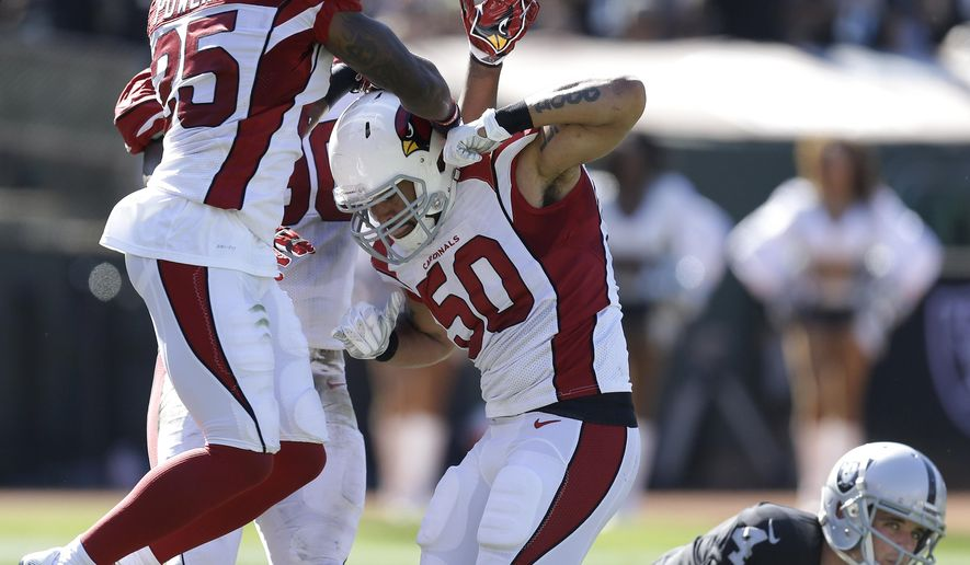 Arizona Cardinals middle linebacker Larry Foote (50) is congratulated by Arizona Cardinals cornerback Jerraud Powers (25) and defensive end Kareem Martin, left rear, after sacking Oakland Raiders quarterback Derek Carr (4) during the second quarter of an NFL football game in Oakland, Calif., Sunday, Oct. 19, 2014. The Cardinals won 24-13. (AP Photo/Ben Margot)