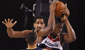 Washington Wizards' Kevin Seraphin, right, is squeezed between New Orleans Pelicans' Alexis Ajinca, back, and Austin Rivers in the second half of an NBA basketball game  Monday, Oct. 20, 2014, in Baltimore.(AP Photo/Gail Burton)