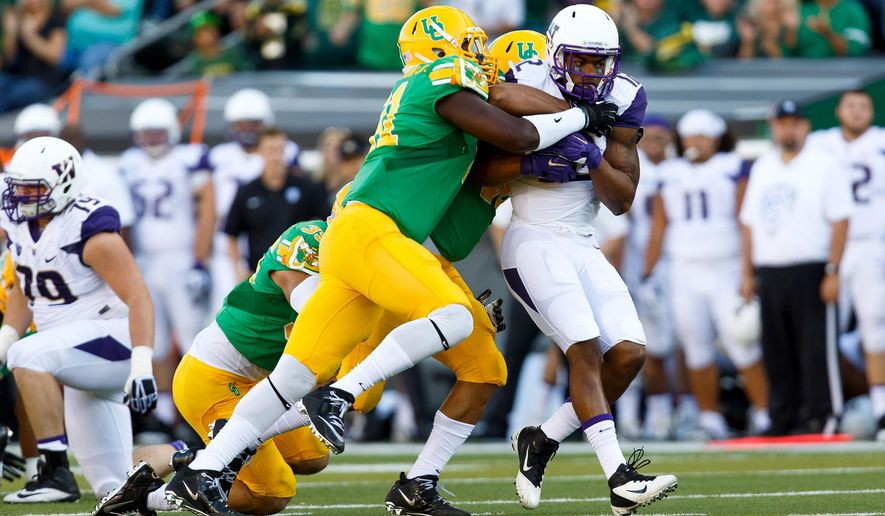 Oregon linebacker Tony Washington (91) stops Washington running back Dwayne Washington (12) during the first quarter in an NCAA college football game in Eugene, Ore., Saturday, Oct. 18, 2014. (AP Photo/Ryan Kang)
