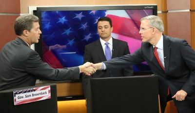 Kansas Governor Sam Brownback and Democratic candidate for governor Paul Davis shake hands after a debate hosted by KWCH-TV Monday, Oct. 20, 2014, at Intrust Bank Arena in Wichita, Kan. (AP Photo/The Wichita Eagle, Jaime Green)