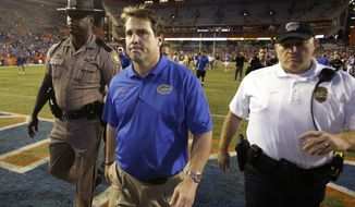 Florida coach Will Muschamp, center, leaves the field after Florida lost to Missouri, 42-13, in an NCAA college football game in Gainesville, Fla., Saturday, Oct. 18, 2014. (AP Photo/John Raoux)