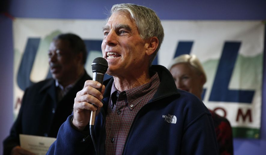 Shortly before mailing his own ballot, U.S. Senator Mark Udall, D-Colo., speaks inside a coffee shop on a campaign stop to remind voters to mail in their ballots, in the Five Points area of Denver, Monday, Oct. 20, 2014. (AP Photo/Brennan Linsley)