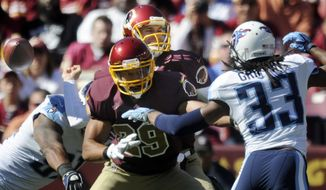 Washington Redskins quarterback Kirk Cousins (8) is sacked by Tennessee Titans outside linebacker Derrick Morgan (91) and turns over the ball in the first quarter at FedExField, Landover, Md., Oct. 19, 2014. (Preston Keres/Special for The Washington Times)