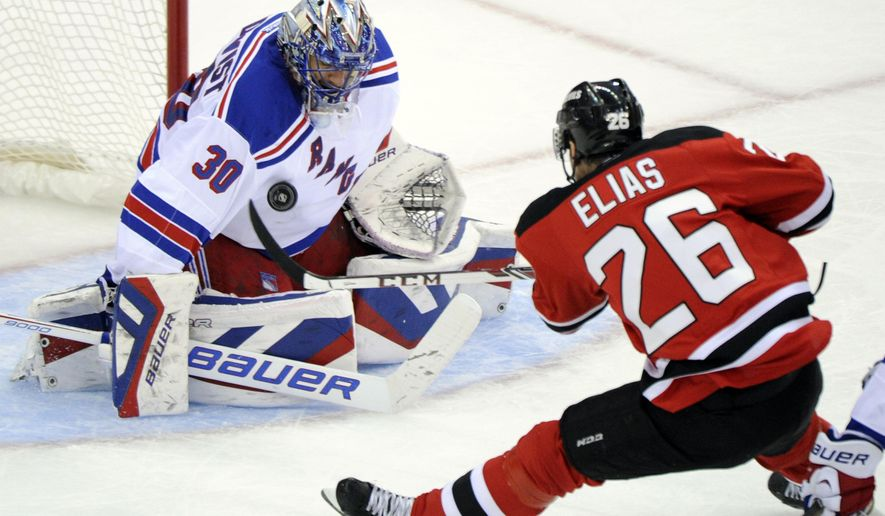 New York Rangers goaltender Henrik Lundqvist, of Sweden, makes a save on a shot by New Jersey Devils' Patrik Elias (26), of the Czech Republic, during the second period of an NHL hockey game Tuesday, Oct. 21, 2014, in Newark, N.J. (AP Photo/Bill Kostroun)