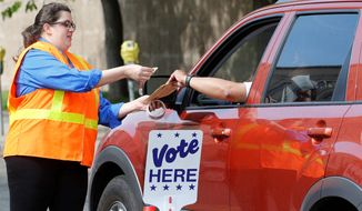 """Election worker Elizabeth Littlepage collects a mail-in ballot from a voter at the Denver Election Division in June. Concerns are running high over door-to-door campaign workers asking voters for their mail-in ballots in what's known as """"ballot harvesting."""" (Associated Press)"""