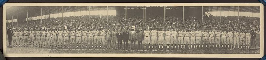 """Group portrait of players from the Kansas City Monarchs and the Hilldale Negro League baseball teams in front of grandstands filled with spectators before the opening game of the inaugural """"Colored World Series"""" in 1924. (Photo by J.E. Miller via Library of Congress)"""