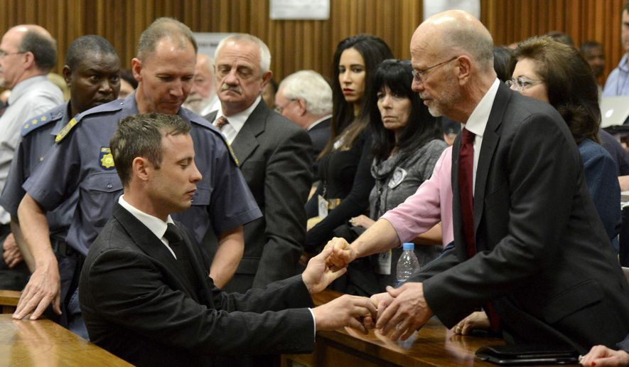 Oscar Pistorius, left front, greets his uncle Arnold Pistorius, right, and other family members as he is led out of court in Pretoria, South Africa, Tuesday, Oct. 21, 2014. Pistorius received a five-year prison sentence for culpable homicide by judge Thokozile Masipais for the killing of his girlfriend Reeva Steenkamp last year (AP Photo/Herman Verwey, Pool)
