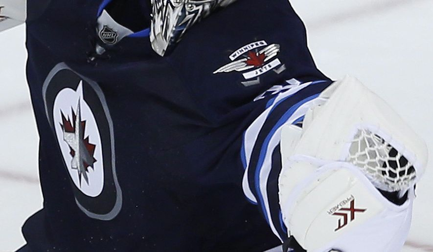 Winnipeg Jets goaltender Ondrej Pavelec keeps a close eye on the puck as he gets a glove on a Carolina Hurricanes shot during the third period of an NHL hockey game Tuesday, Oct. 21, 2014, in Winnipeg, Manitoba. (AP Photo/The Canadian Press, John Woods)