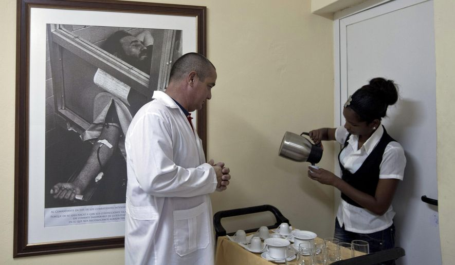 Cuban Doctor Ronald Hernandez is served coffee before the start of a press event in Havana, Cuba, Tuesday, Oct. 21, 2014. Some of the 91 health workers who will travel to Liberia and Guinea to help with the treatment of Ebola patients were presented to the press. Cuba's government says they have already sent 165 healthcare workers to Sierra Leone. On the wall is a photograph of Fidel Castro donating blood during a blood drive after a 1970 earthquake in Peru. (AP Photo/Franklin Reyes)