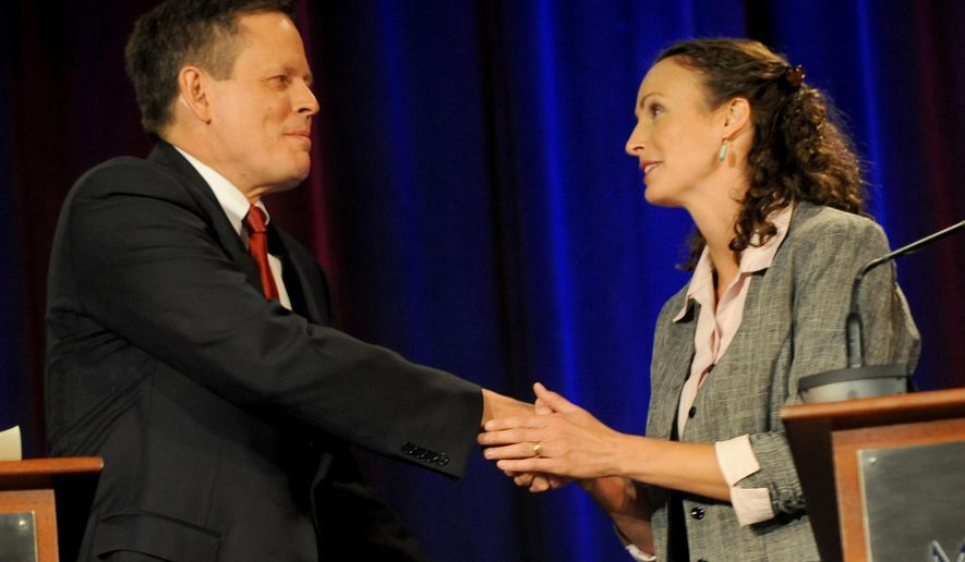 U.S. Rep. Steve Daines and Montana State Rep. Amanda Curtis shake hands after a political debate Monday, Oct. 20, 2014, in Billings, Mont. (AP Photo/The Billings Gazette, Hannah Potes)
