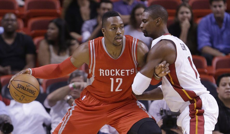Houston Rockets center Dwight Howard (12) drives up against Miami Heat forward Chris Bosh during the first half of a preseason NBA basketball game, Tuesday, Oct. 21, 2014 in Miami. (AP Photo/Wilfredo Lee)