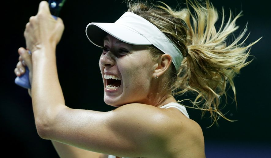 Russia's Maria Sharapova makes a backhand return to Denmark's Caroline Wozniacki during their singles match at the WTA tennis finals in Singapore,Tuesday, Oct. 21, 2014. (AP Photo/Mark Baker)