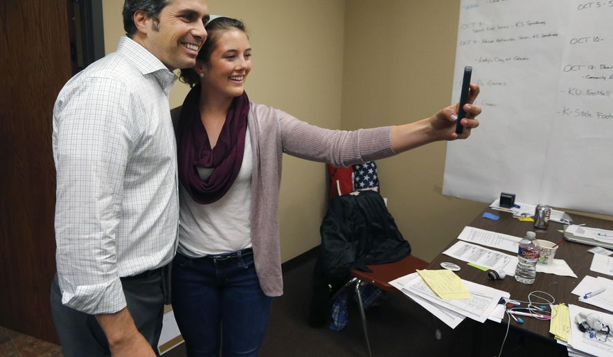 In this Oct. 9, 2014 photo volunteer Carley Olson, right, takes a selfie with Independent Kansas Senate candidate Greg Orman at the Orman for Senate Headquarters in Shawnee, Kan. Orman has had barely a month to introduce himself to Kansas voters since unusual events thrust him into a neck-and-neck competition with three-term Republican Sen. Pat Roberts. Yet the independent candidate's schedule of public campaign appearances has usually ranged from slim to none. (AP Photo/Orlin Wagner)