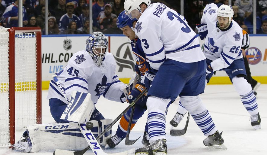Toronto Maple Leafs goalie Jonathan Bernier (45) makes a stick save with New York Islanders center Casey Cizikas (53) challenging and Maple Leafs' Dion Phaneuf (3) defending during the second period of an NHL hockey game in Uniondale, N.Y., Tuesday, Oct. 21, 2014. (AP Photo/Kathy Willens)