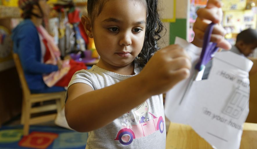 Isis Morton, 4, works with scissors and paper at a desk in a Pre-Kindergarten class at the Community Day Center for Children, during class Tuesday, Oct. 21, 2014, in Seattle. Two Seattle ballot proposals that could both benefit thousands of preschool children are competing against each other for votes in the upcoming November election. (AP Photo/Ted S. Warren)