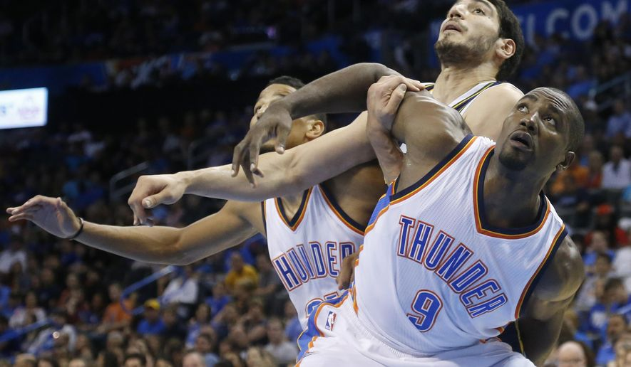 Oklahoma City Thunder forward Serge Ibaka (9) fights for position with Utah Jazz center Enes Kanter, center, in front of Thunder forward Andre Roberson during the second quarter of a preseason NBA basketball game in Oklahoma City, Tuesday, Oct. 21, 2014. (AP Photo/Sue Ogrocki)