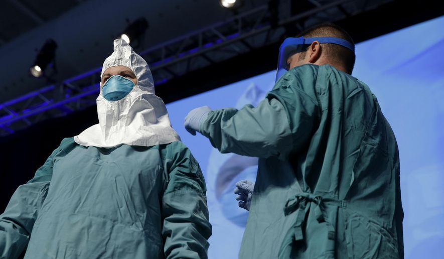 Nurse Barbara Smith, left, and Dr. Bryan Christensen demonstrate the proper way for health care workers to use personal protective equipment when dealing with Ebola during an education session in New York, Tuesday, Oct. 21, 2014. Thousands of participants, mostly health care workers, attended the session to review basic facts about Ebola and updated guidelines for protection against its spread. (AP Photo/Seth Wenig)