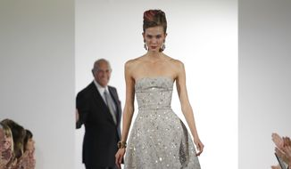 In this Sept. 11, 2012, file photo, fashion designer Oscar de la Renta watches as the final model walks the runway during the presentation of his Spring 2013 collection at Fashion Week in New York.  The designer de la Renta, a favorite of socialites and movie stars alike, has died. He was 82.  (AP Photo/Kathy Willens, File)