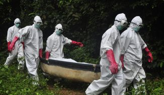 In this Saturday, Oct. 18, 2014, file photo, a burial team in protective gear carry the body of woman suspected to have died from the Ebola virus in Monrovia, Liberia. (AP Photo/Abbas Dulleh, File)