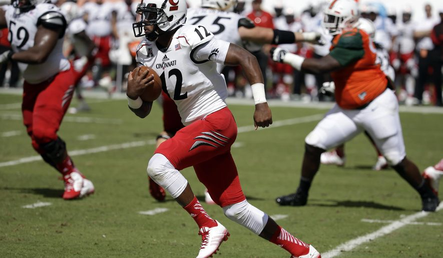 FILE - In this Oct. 11, 2014, file photo, Cincinnati quarterback Jarred Evans (12) runs in the second half of an NCAA college football game against Miami in Miami Gardens, Fla. Hamilton County Jail records show 22-year-old Jarred Evans was booked just before 4 a.m. Sunday, Oct. 19, 2014,  on a misdemeanor assault charge. Police said Evans knocked a man down with a punch that caused a concussion and cuts requiring stitches. (AP Photo/Lynne Sladky, File)