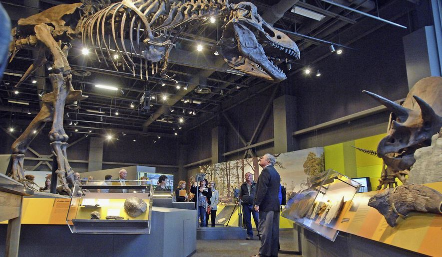 FILE - In this April 28, 2014  file photo, Gov. Jack Dalrymple looks up at a Tyrannosaurus Rex during a tour of the North Dakota Heritage Center and Museum in Bismarck, N.D. State Historical Society leaders say they're confident that the bulk of the work will be done when the expanded Heritage Center on the North Dakota Capitol grounds holds its grand opening celebration on Nov. 2, the 125th anniversary of North Dakota statehood. (AP Photo/The Bismarck Tribune, Tom Stromme, File)