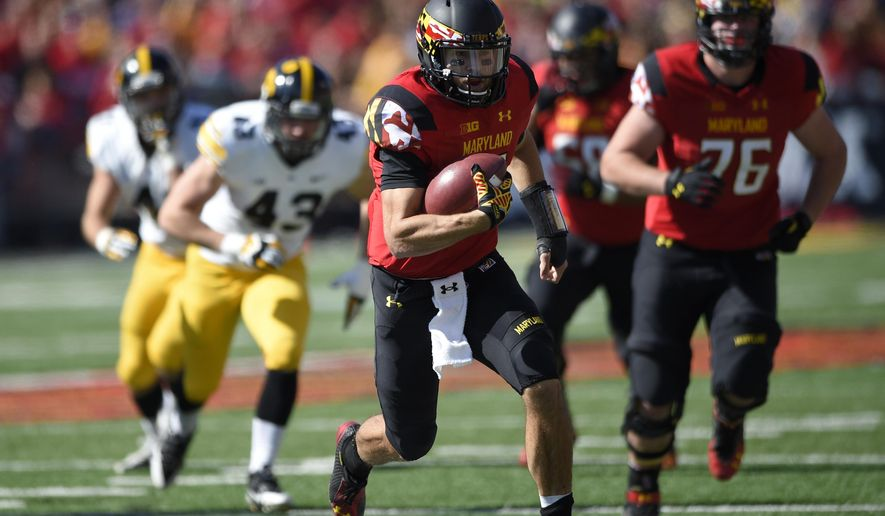 Maryland quarterback C.J. Brown, center, runs with the ball against Iowa during the first half of an NCAA college football game, Saturday, Oct. 18, 2014, in College Park, Md. Maryland won 38-31. Also seen is Maryland offensive lineman Michael Dunn (76). (AP Photo/Nick Wass)