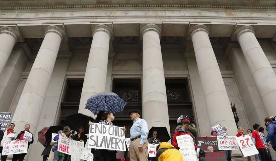 People opposed to child sex trafficking rally outside of the Washington state Supreme Court on Tuesday, Oct. 21, 2014, in Olympia, Wash. The court was hearing a case filed by three victims who say the website Backpage.com helps promote the exploitation of children. (AP Photo/Rachel La Corte)