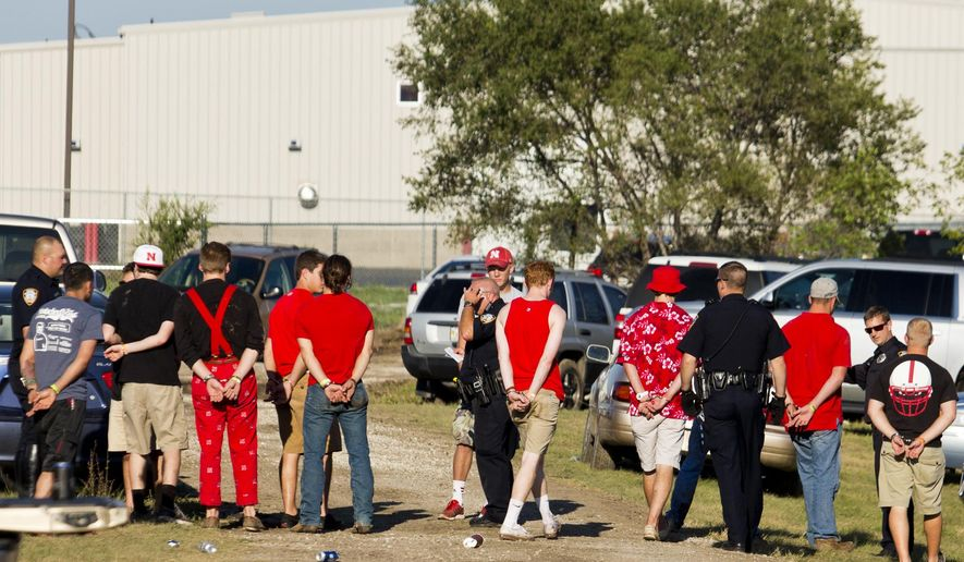 In this Sept. 20, 2014 photo, police make a mass arrest after chaos broke out over tailgating spots at the Indian Center, Lincoln, Neb. The popular Nebraska football tailgating spot has permanently banned alcohol after a violent incident that ended with 13 arrests and sent a police officer to the hospital. (AP Photo/The Journal-Star, Kaylee Everly)