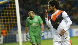 Shakhtar's Luiz Adriano celebrates after scoring against BATE as BATE's goalkeeper Sergei Chernik looks on during their Champions League Group Stage in group H soccer match in Borisov, Belarus, Tuesday, Oct. 21, 2014. (AP Photo/Sergei Grits)