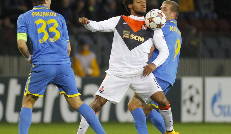 BATE's Denis Polyakov, left, and Ilya Aleksievich, right, vie for the ball against Shakhtar's Luiz Adriano during their Champions League Group Stage in group H soccer match in Borisov, Belarus, Tuesday, Oct. 21, 2014. (AP Photo/Sergei Grits)