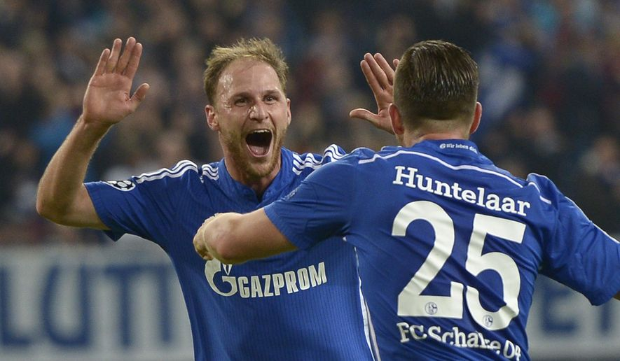 Schalke's Benedikt Hoewedes, left, celebrates with his teammate Klaas Jan Huntelaar, right, after he scored his side's third goal during the Champions League group G soccer match between Schalke 04 and Sporting in Gelsenkirchen, Germany, Tuesday, Oct. 21, 2014.(AP Photo/Martin Meissner)