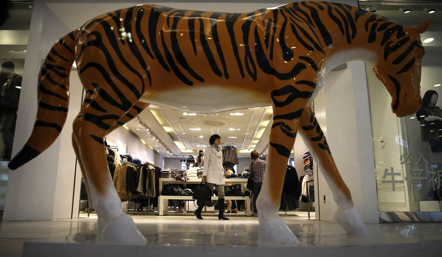 A woman exits a fashion boutique near a horse statue on display inside a shopping mall in Beijing, China Tuesday, Oct. 21, 2014. China's economic growth waned to a five-year low of 7.3 percent last quarter, raising concerns of a spillover effect on the global economy but falling roughly in line with Chinese leaders' plans for a controlled slowdown. (AP Photo/Andy Wong)