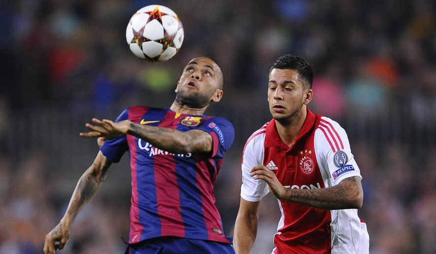 Barcelona's Dani Alves, left controls the ball in front of Ajax's Ricardo Kishna during the Champions League group F soccer match between F.C. Barcelona and Ajax at the Camp Nou stadium in Barcelona, Spain, Tuesday, Oct. 21, 2014. (AP Photo/Manu Fernandez)