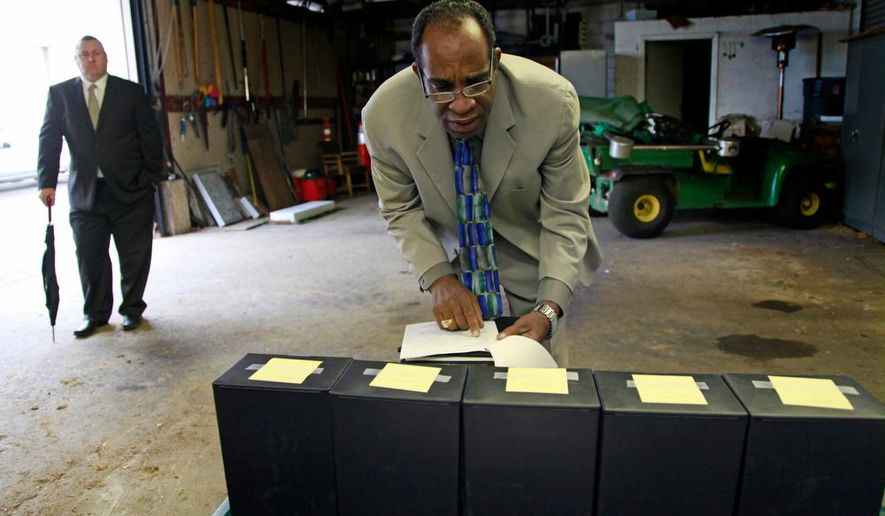 In this Monday, Oct. 20, 2014 photo, Jim Jones Jr. checks the names on five boxes carrying the remains of victims of the Jonestown, Guyana mass suicide-murder as Ron Haulman, left, Executive Director of Evergreen Cemetery, left, looks on in Oakland, Calif. Five victims of the 1978 mass suicide-murder in Jonestown, Guyana whose cremated remains were recently discovered inside an abandoned Delaware funeral home were laid to rest Monday in a grave in Oakland where more than 400 other unclaimed or unidentified Jonestown victims are interred. (AP Photo/Bay Area News Group, Laura A. Oda)