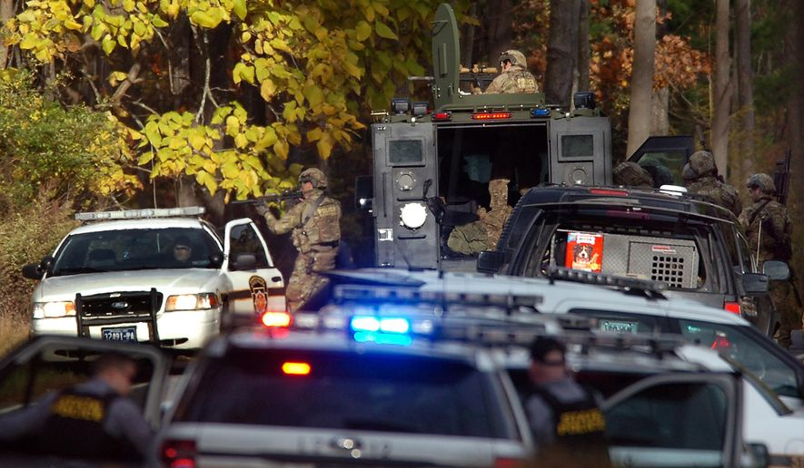 U.S. Marshals Service members aim their rifles toward the woods on Lower Swiftwater Road on Saturday, Oct. 18, 2014, in Swiftwater, Pa., during a massive manhunt for killer Eric Frein.   (AP Photo / The Scranton Times-Tribune, Butch Comegys)