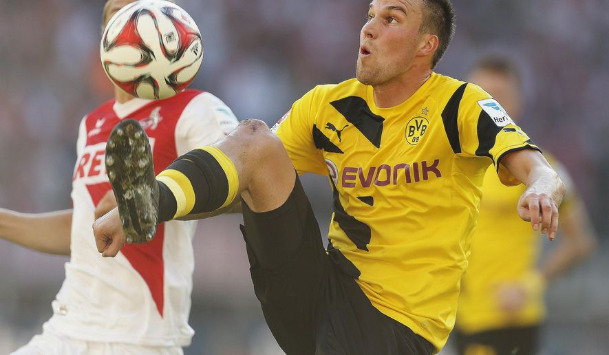Dortmund's Kevin Grosskreutz, right, and Cologne's Marcel Risse challenge for the ball during the German first division Bundesliga soccer match between 1.FC Cologne and BvB Borussia Dortmund in Cologne, Germany, Saturday, Oct. 18, 2014. (AP Photo/Frank Augstein)